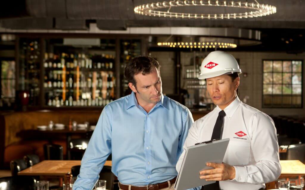 Orkin pest control technician discussing service in a bar environment