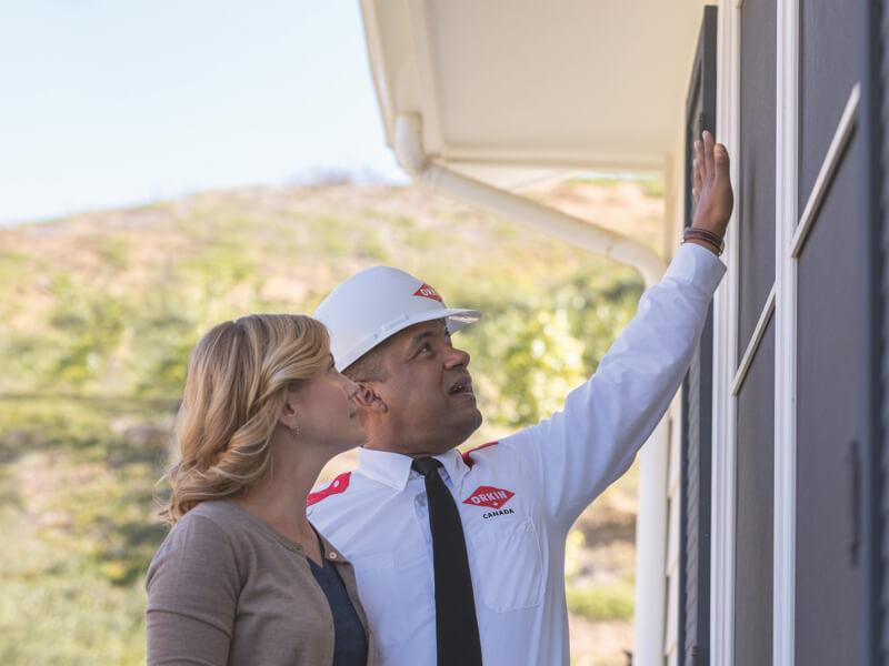 Orkin Technician doing an exterior home inspection with the home owner